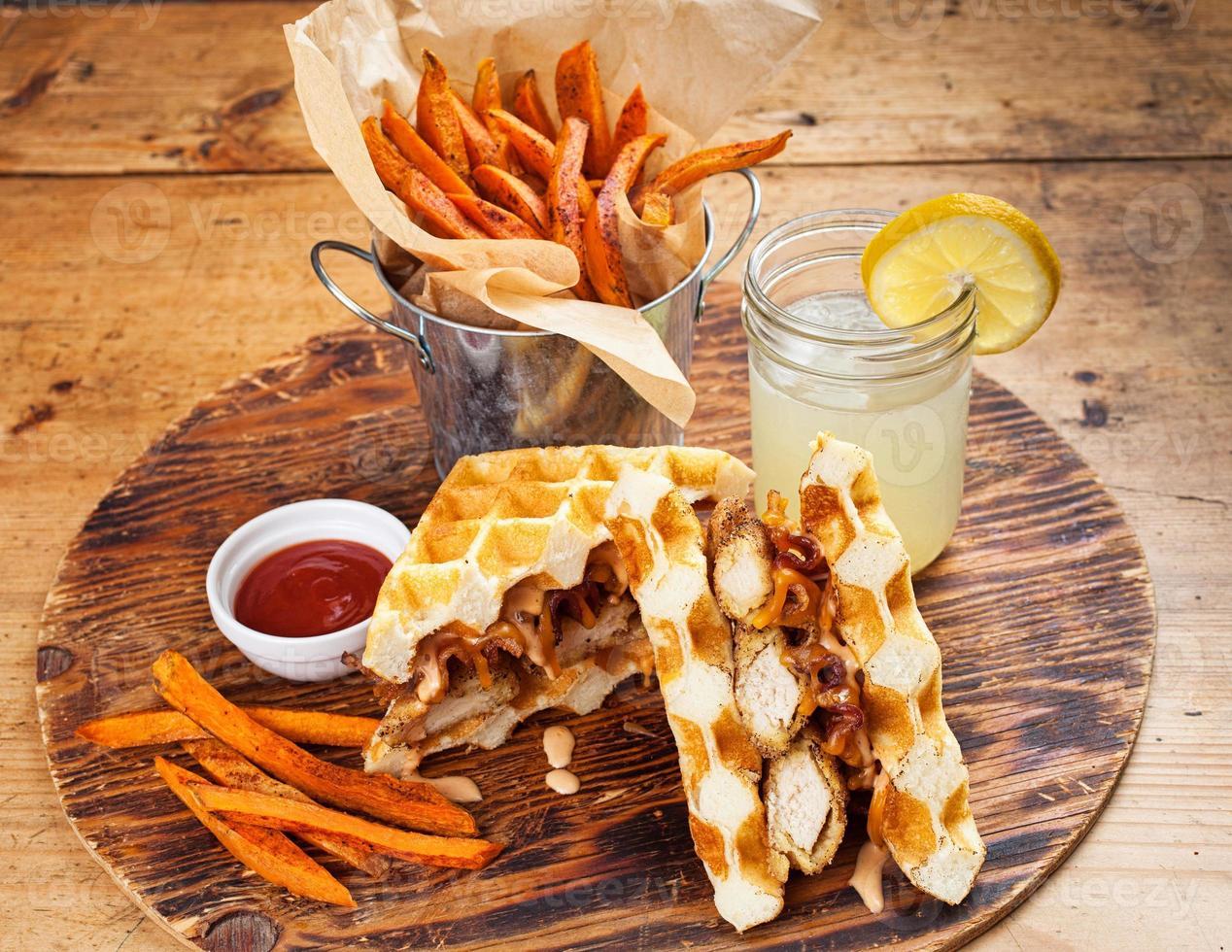 sanduíche de frango e waffle com batatas fritas foto
