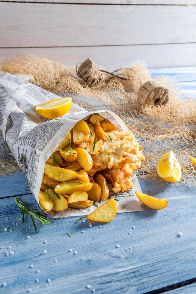 bacalhau de peixe quente com batatas fritas no jornal com limão foto