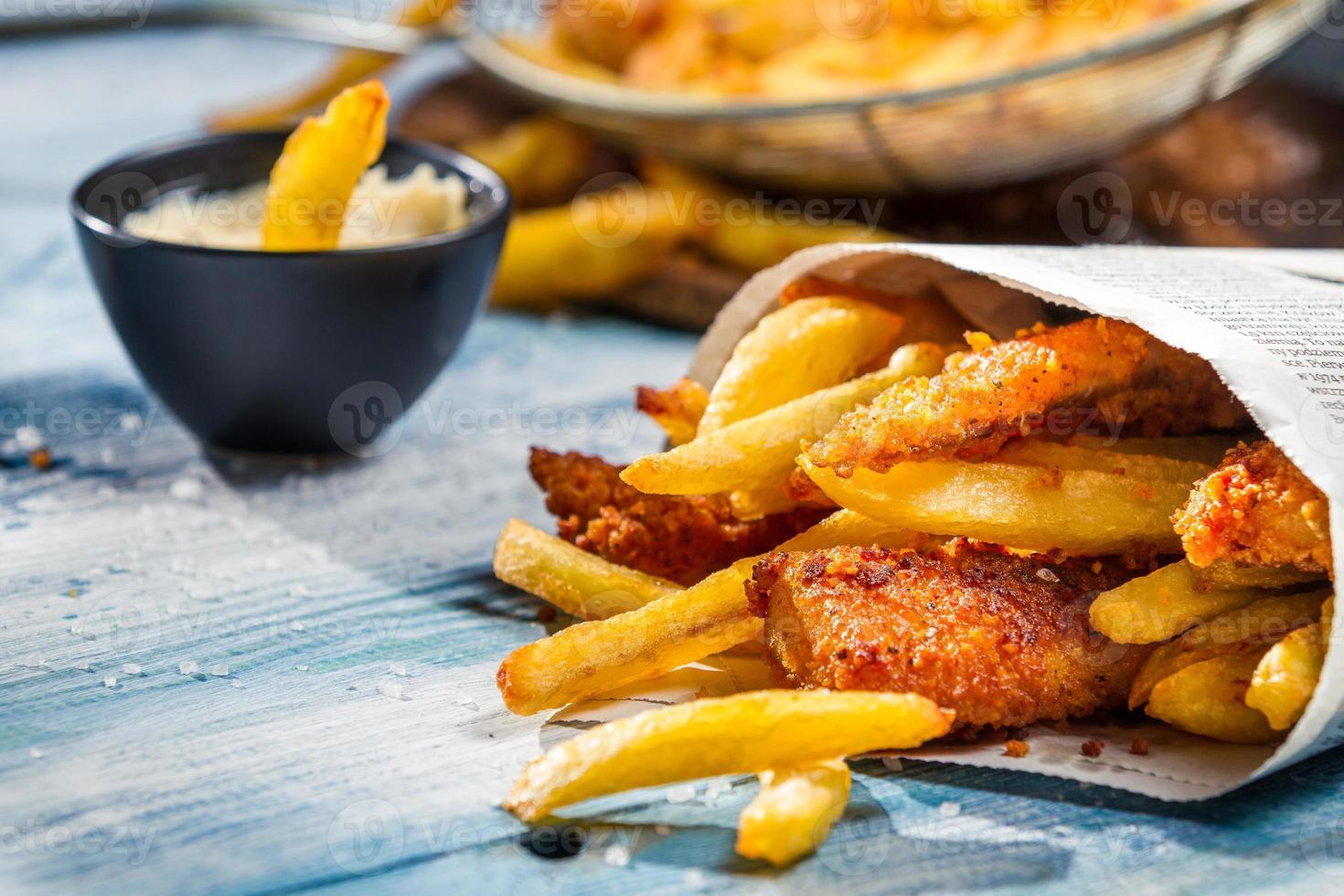 closeup de peixe e batatas fritas, servido no jornal foto
