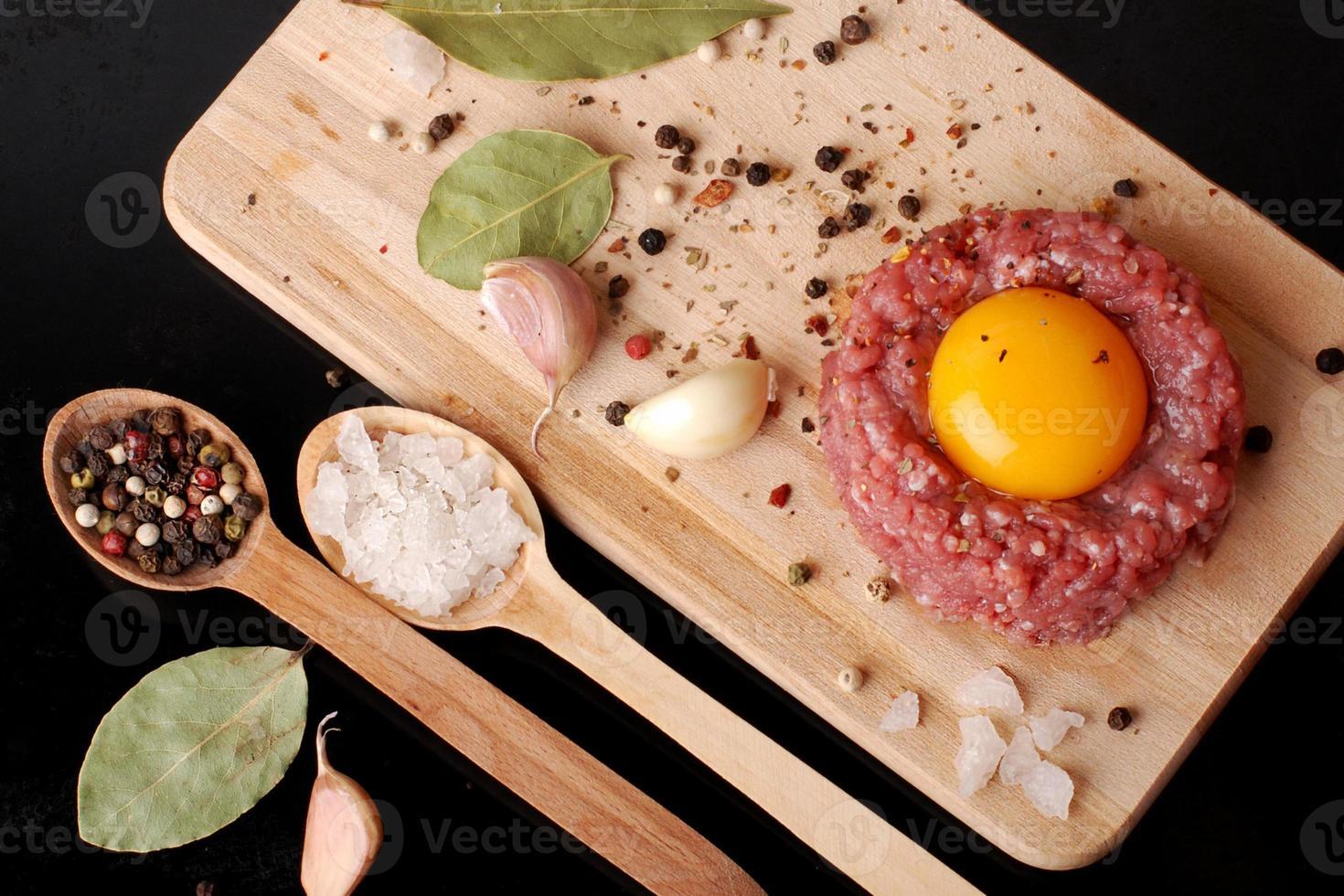 carne picada com especiarias em uma superfície de madeira velha foto