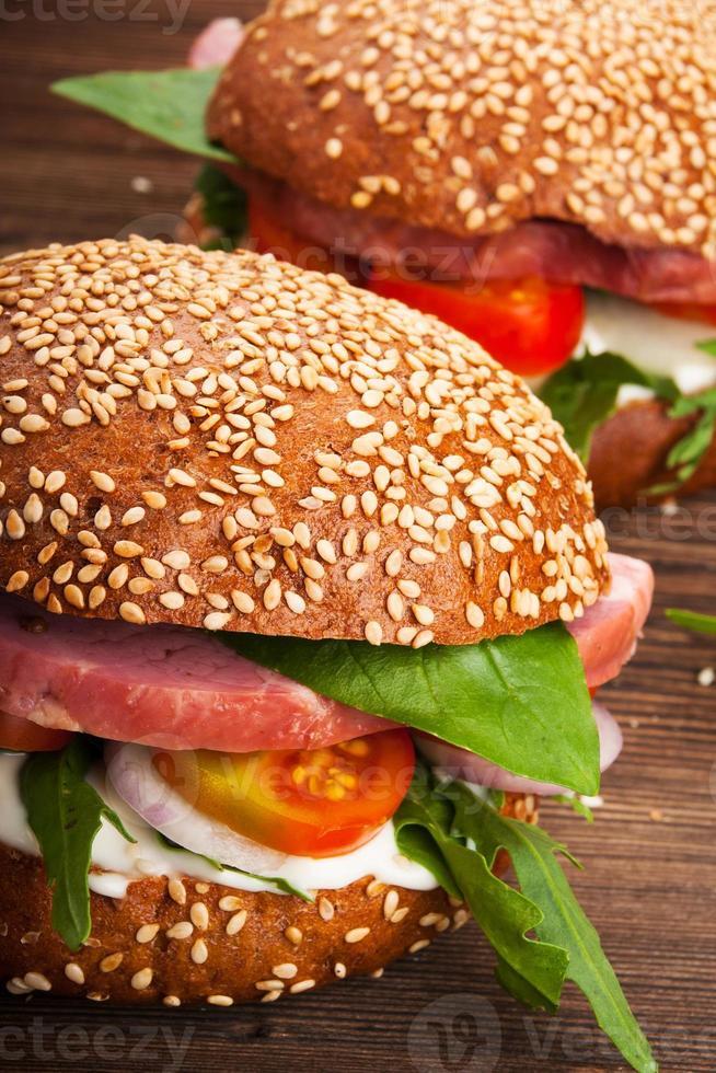 hambúrguer com bacon, rúcula e tomate em fundo rústico de madeira foto