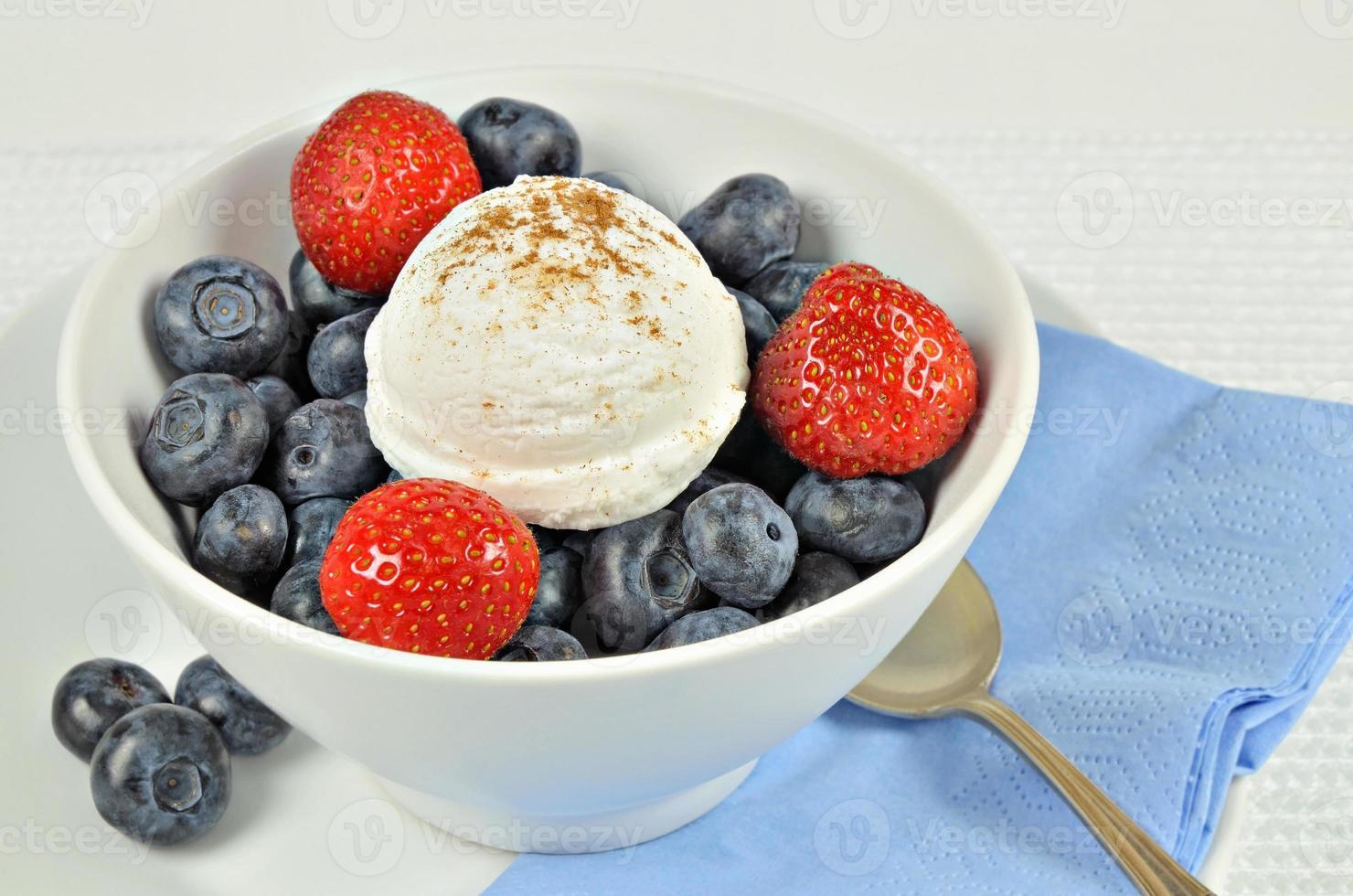sorvete de baunilha com morangos e mirtilos foto