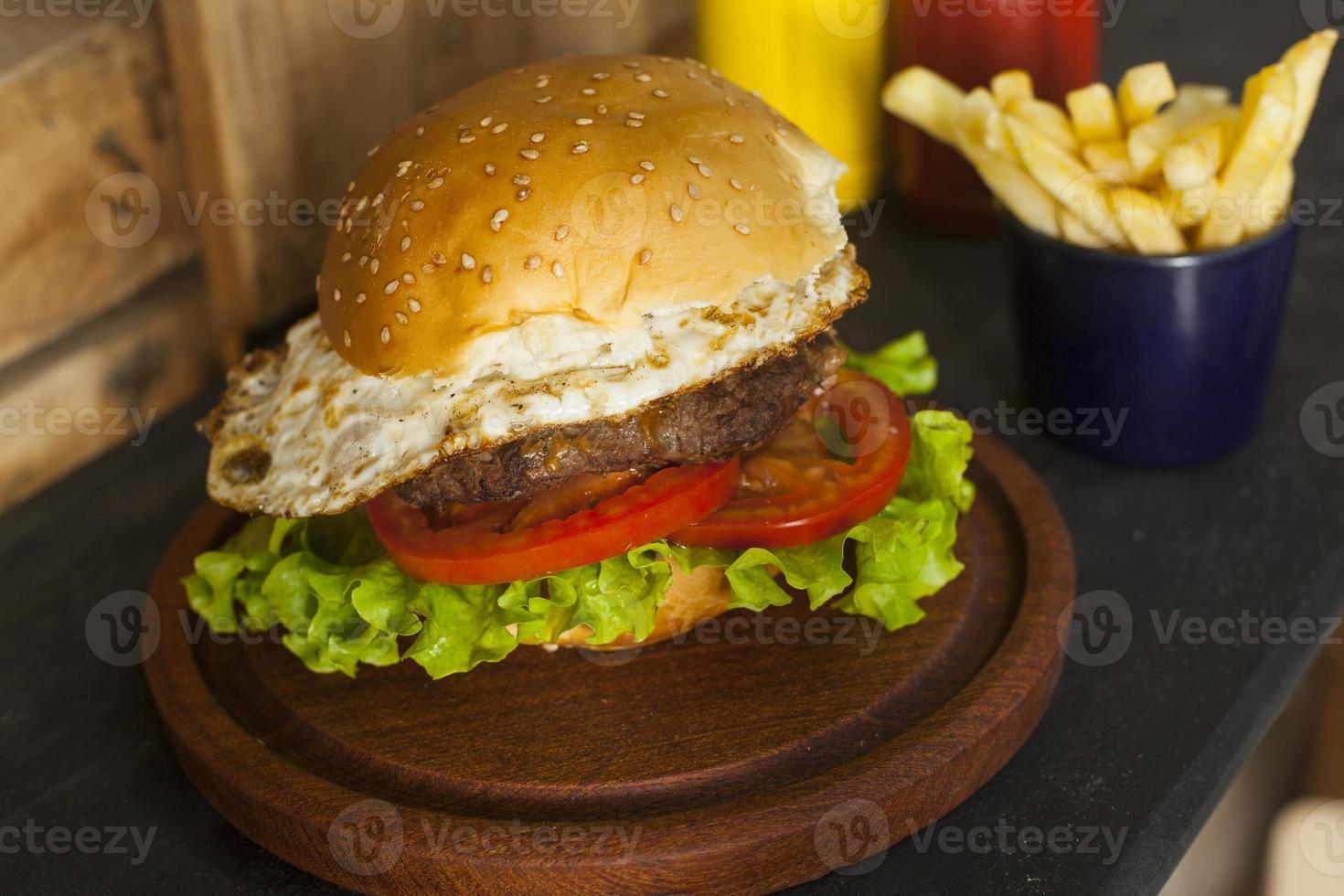 hambúrguer com batatas fritas na mesa de madeira foto