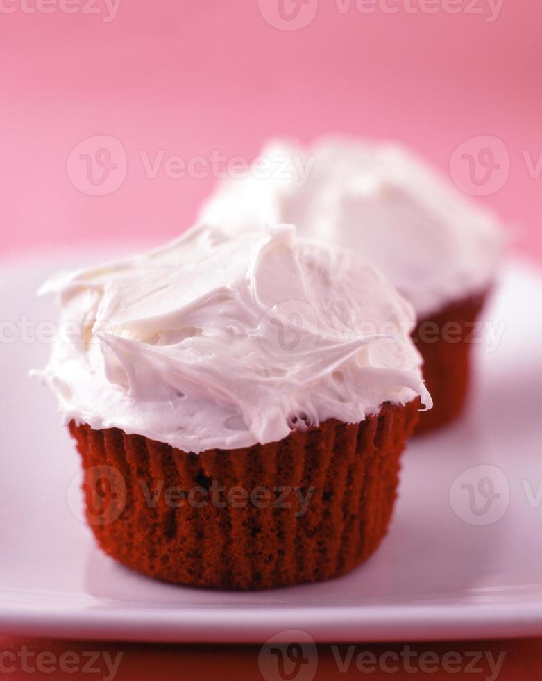 cupcakes de veludo vermelho com cobertura de baunilha foto