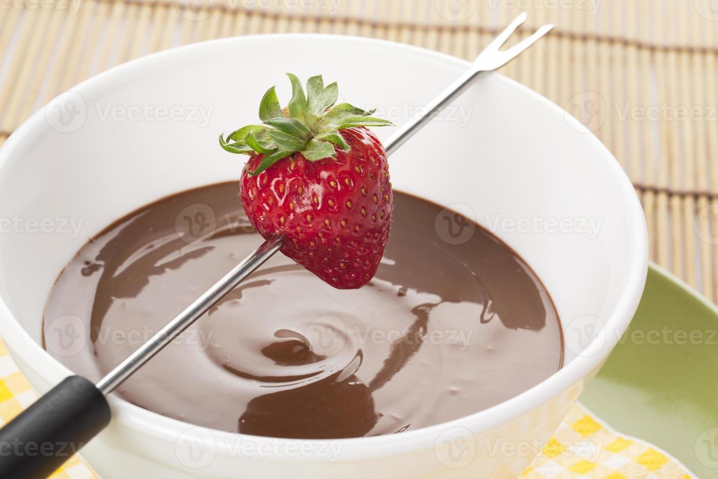 morango no palito de fondue e tigela de chocolate derretido foto