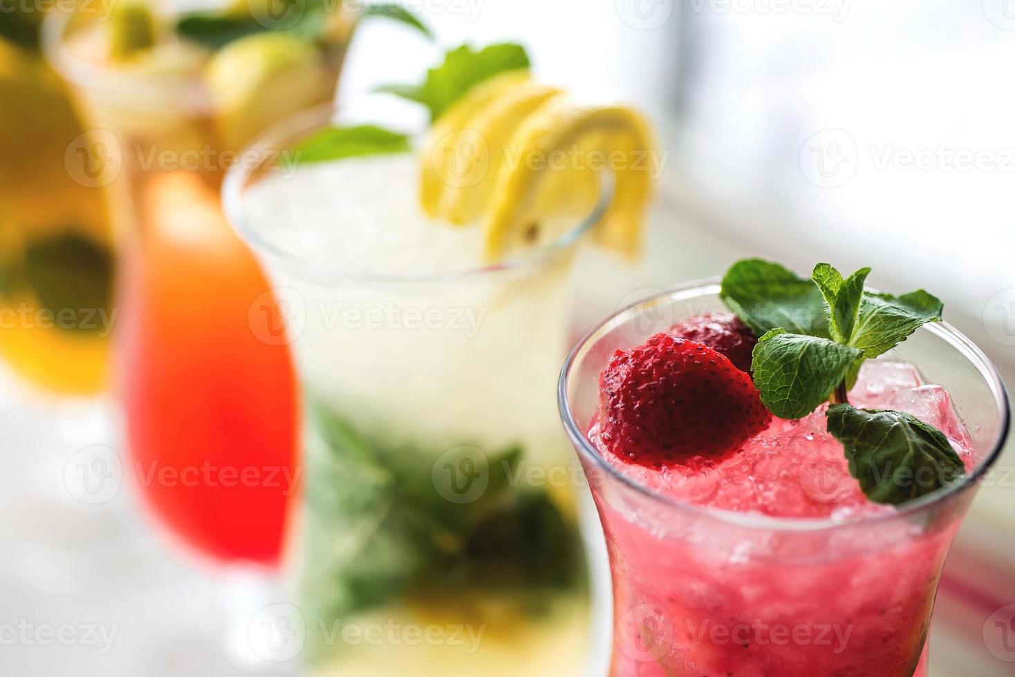 cocktails refrescantes com limão, hortelã, laranja e morango foto