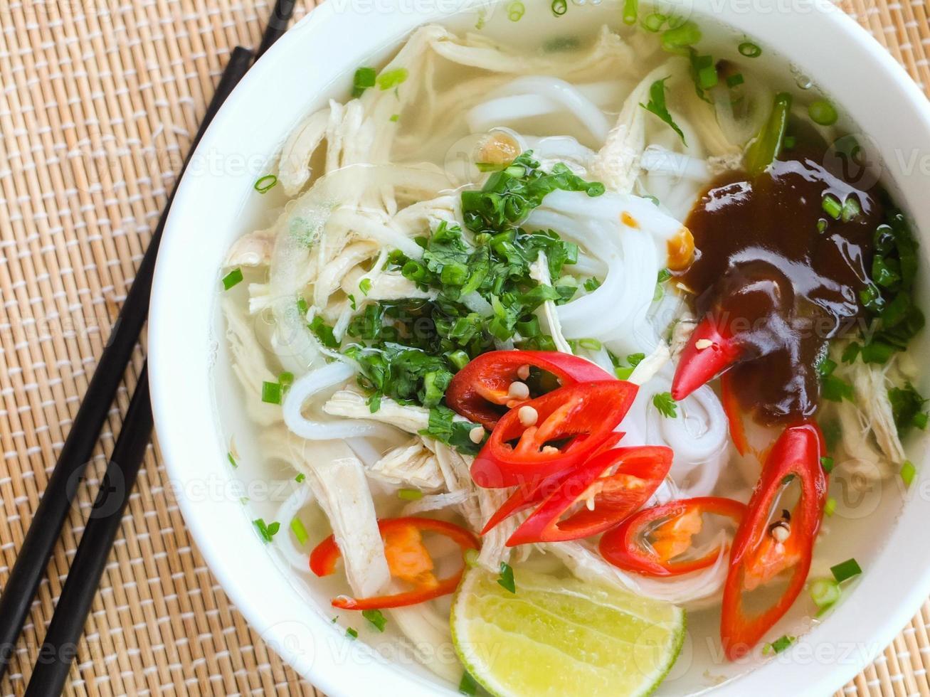 fotografia de sopa de macarrão de arroz de frango asiático com legumes foto
