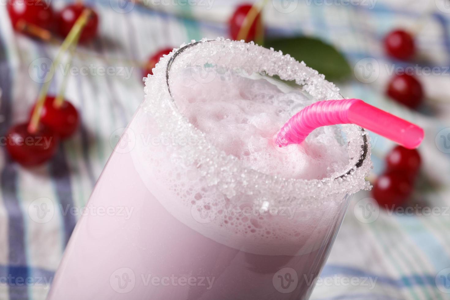 coquetel de leite com uma cereja em uma macro de vidro. horizontal foto