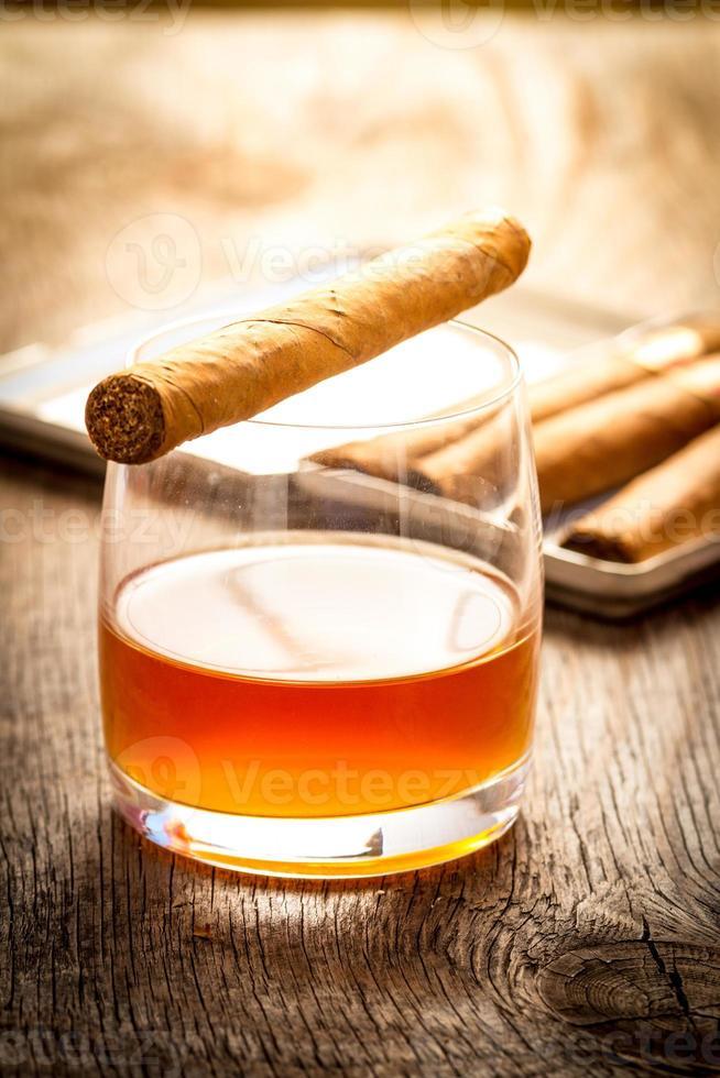 charutos cubanos na mesa de madeira com copo de rum foto
