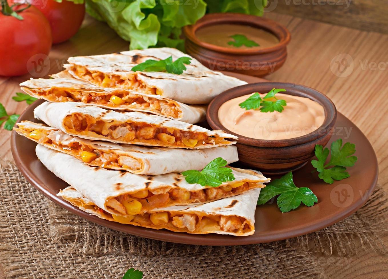 quesadilla mexicano fatiado com legumes e molhos foto