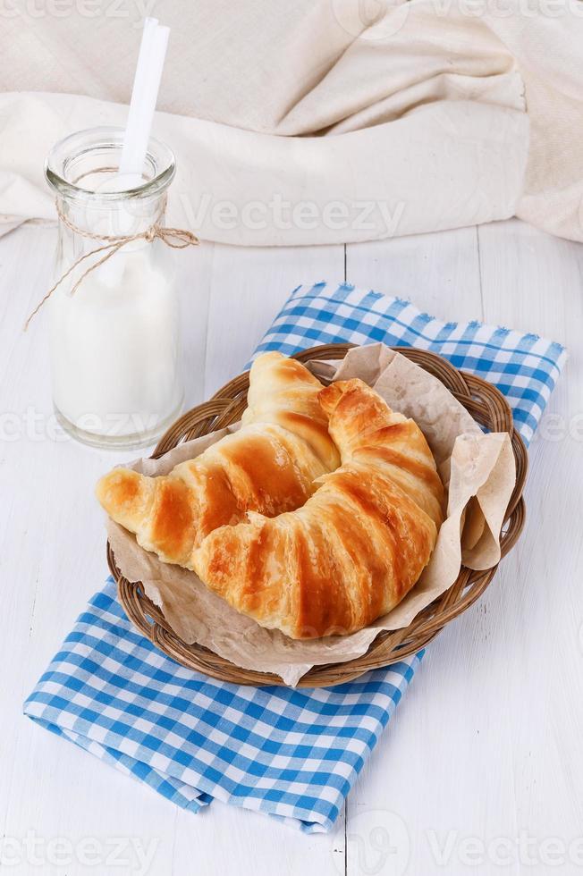 croissants cozidos frescos no prato tecido sobre backgrou de madeira branco foto