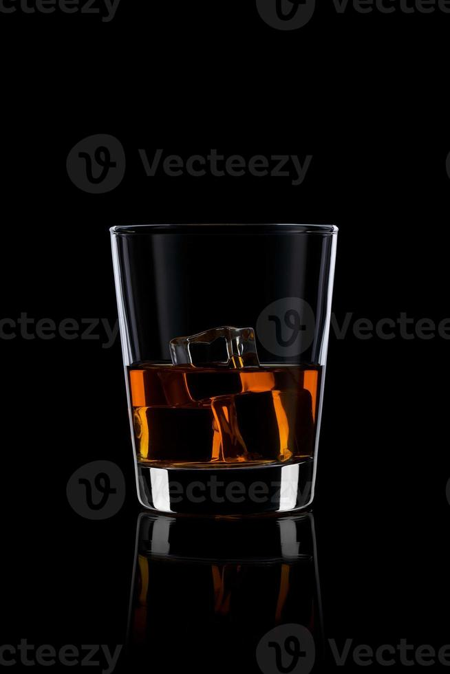 copo com uísque e gelo no preto foto