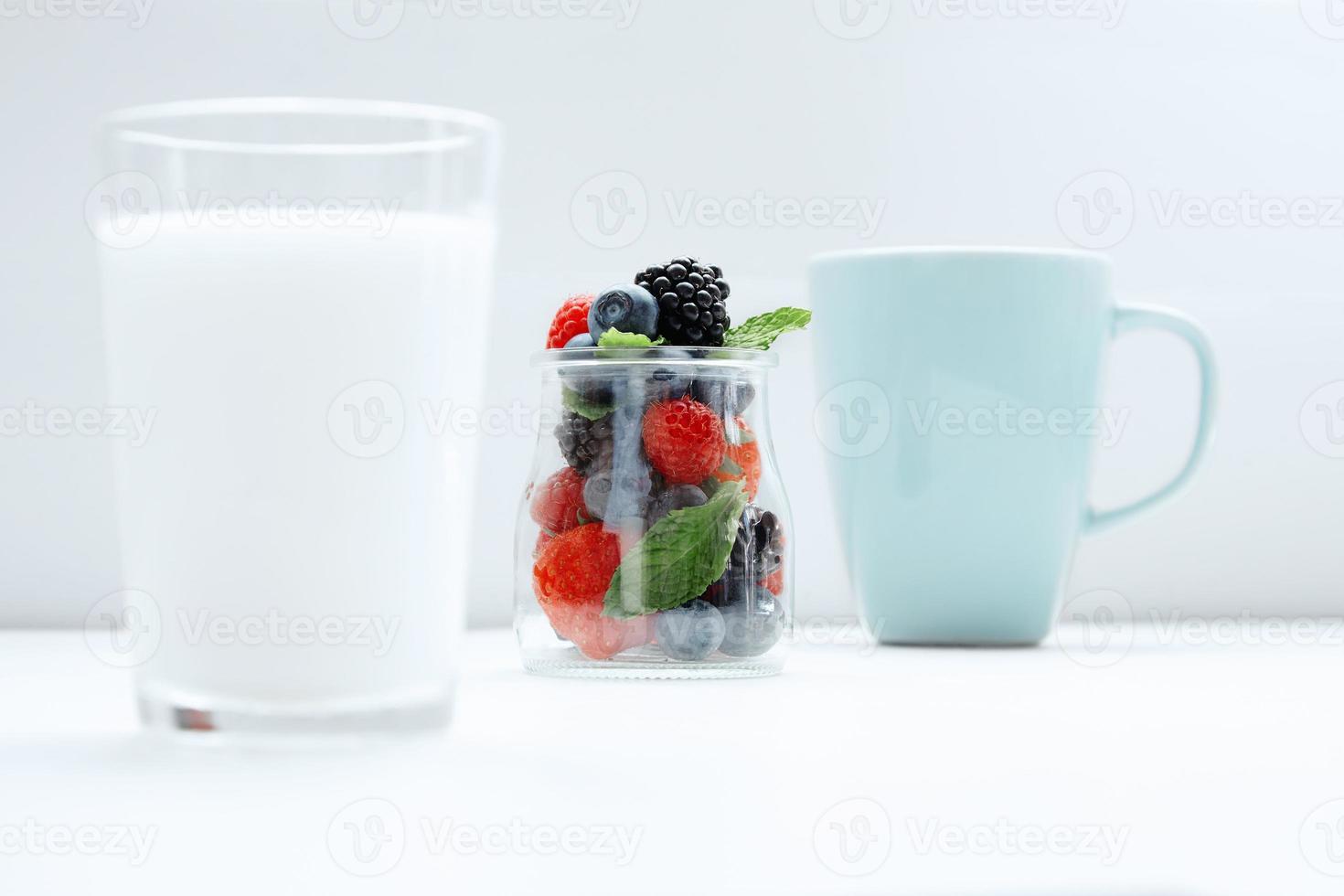 frutas de paralaxe em frasco transparente entre copo de leite foto