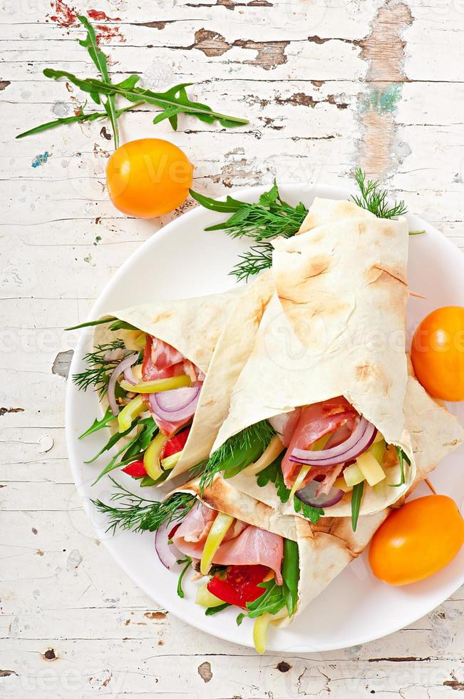 tortilla fresca envolve com carne e legumes no prato foto