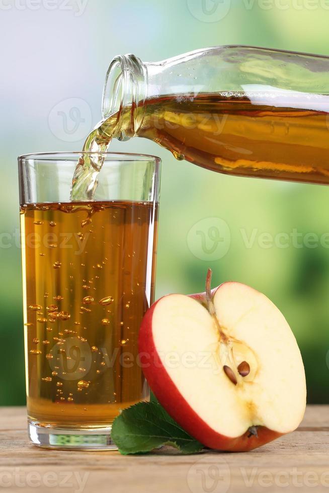 suco de maçã derramando de maçãs em um copo foto