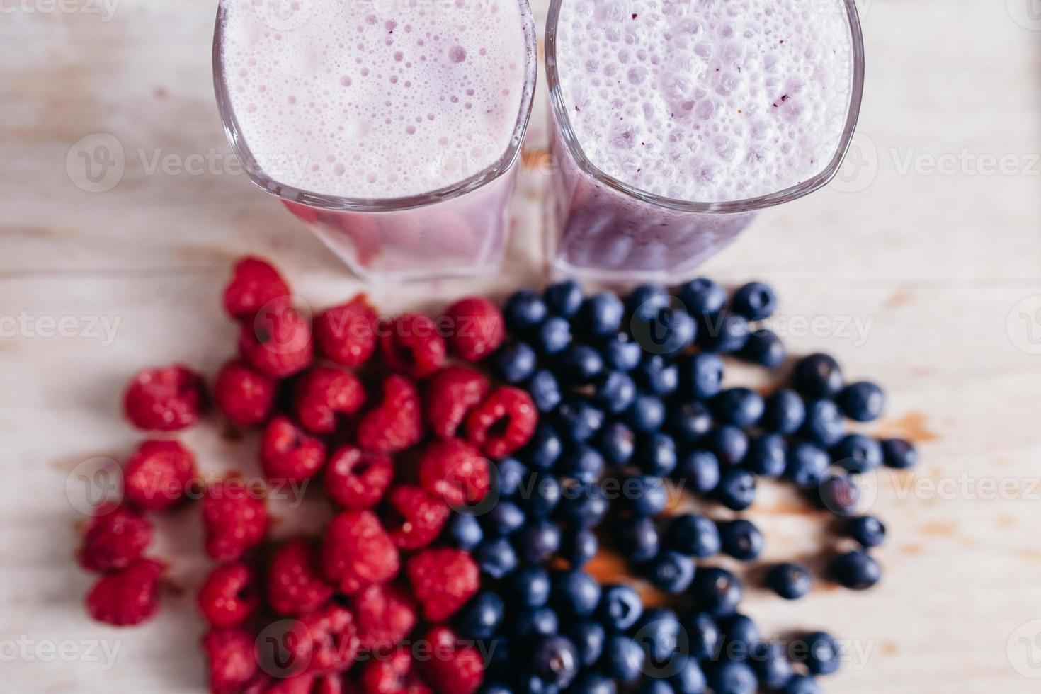 smoothie de framboesa e mirtilo com frutas frescas na madeira tabl foto
