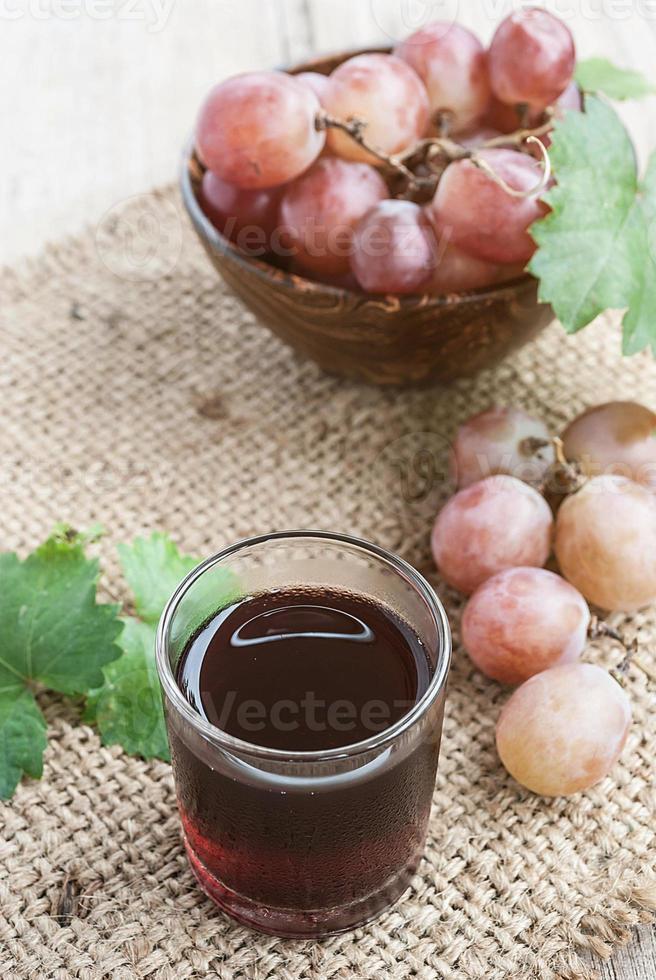 suco de uva vermelho refrigerado com uva vermelha fresca foto