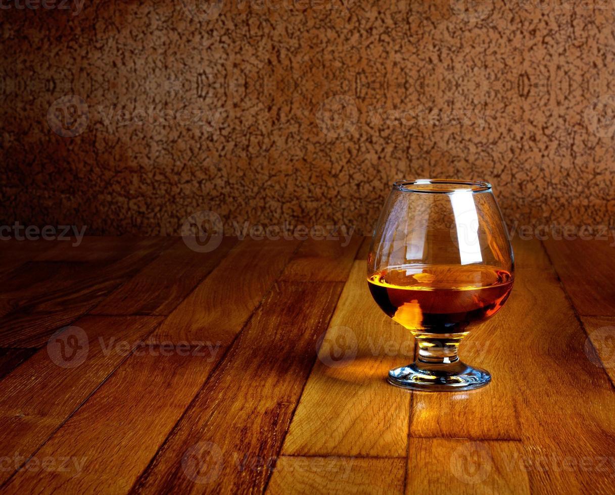 um copo de conhaque na bancada de madeira antiga foto