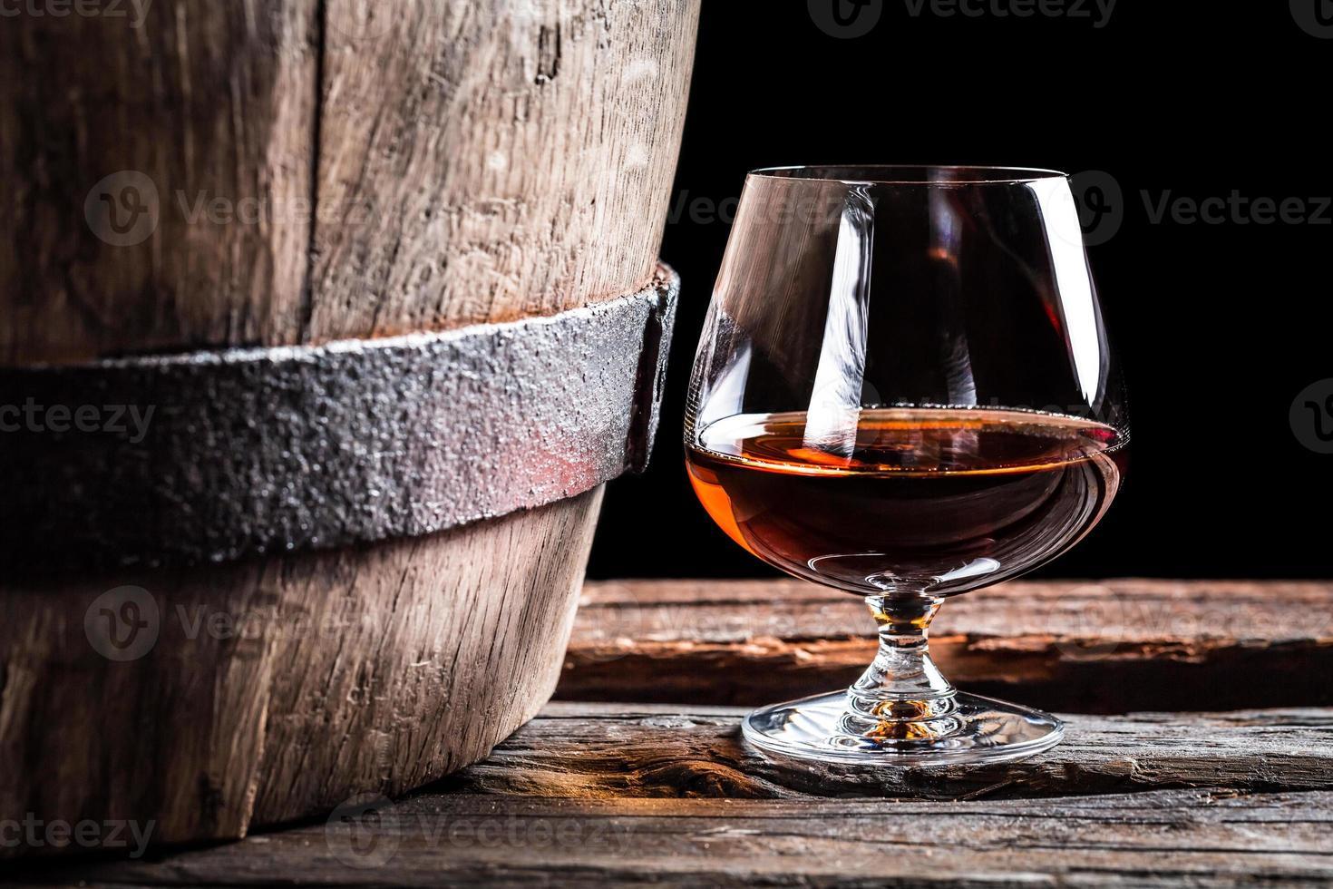 vidro brendy e barril de carvalho velho foto