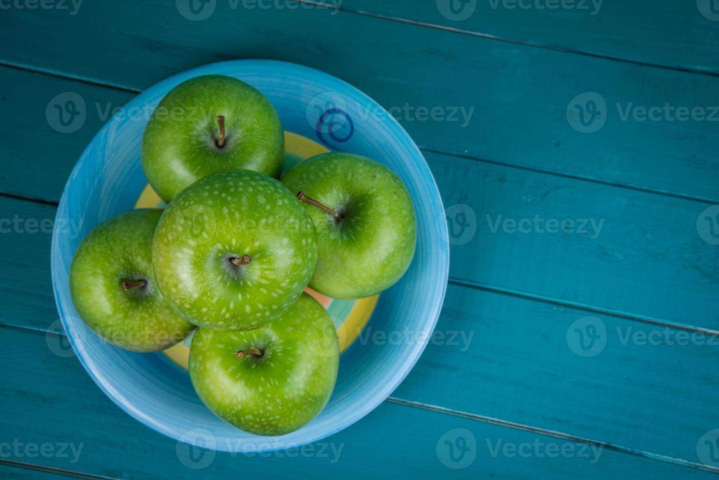 fazenda maçãs orgânicas verdes frescas na mesa azul retrô de madeira foto