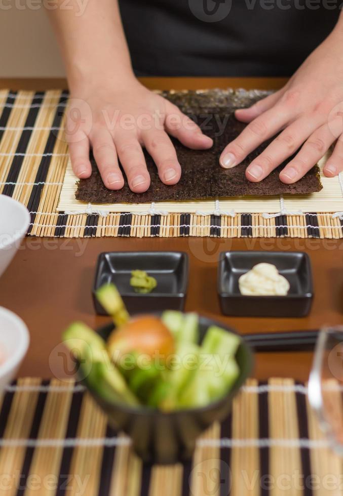 chef de mulher pronto para preparar rolos de sushi japonês foto