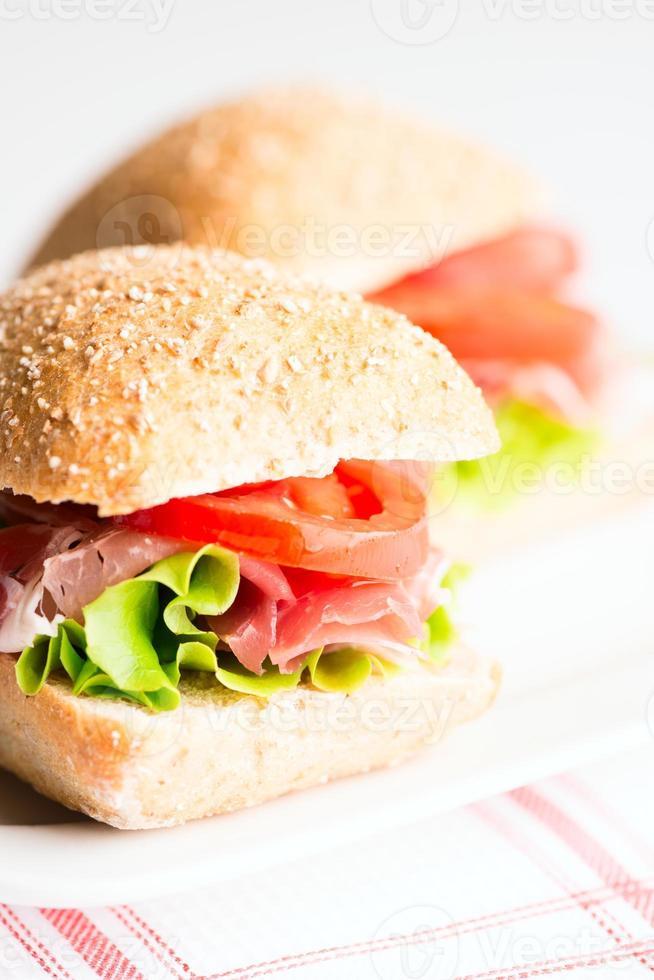 sanduíche de presunto com foco seletivo de tomate e rúcula foto