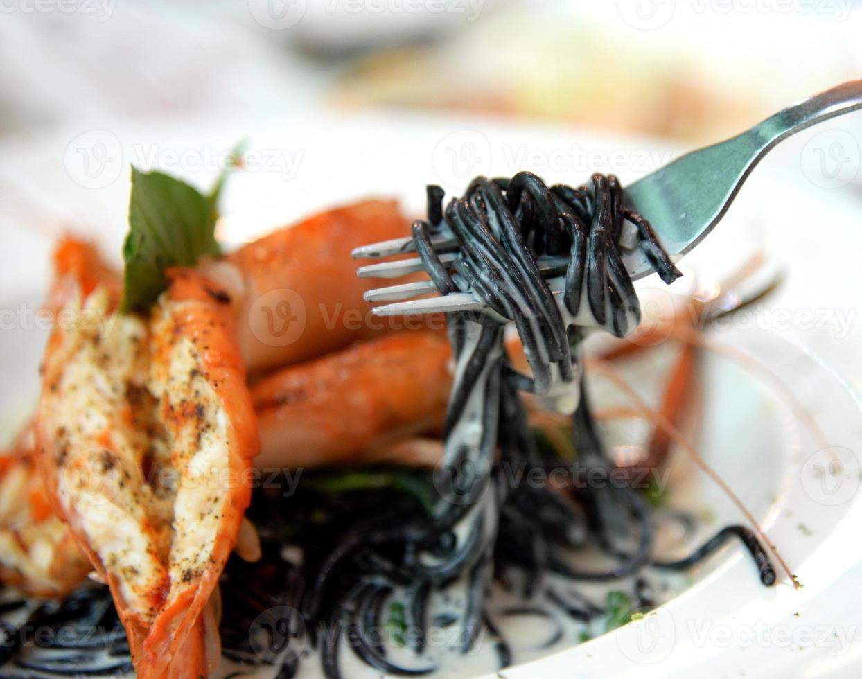 espaguete de macarrão preto com frutos do mar foto
