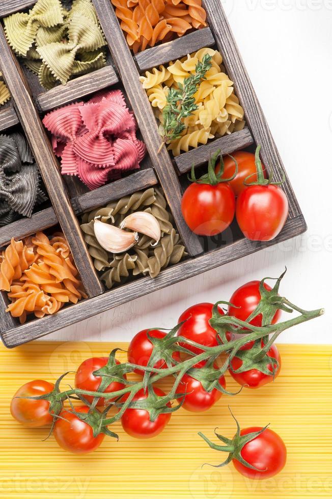 massas italianas sortidas e espaguete tomate em caixa de madeira foto