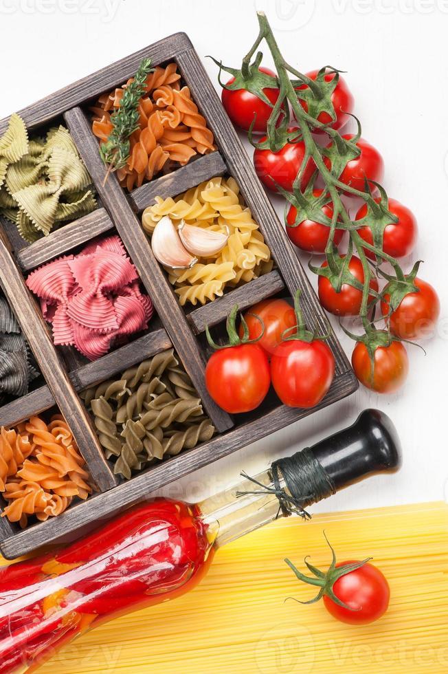 misture os tomates de macarrão e espaguete italiano em caixa de madeira foto