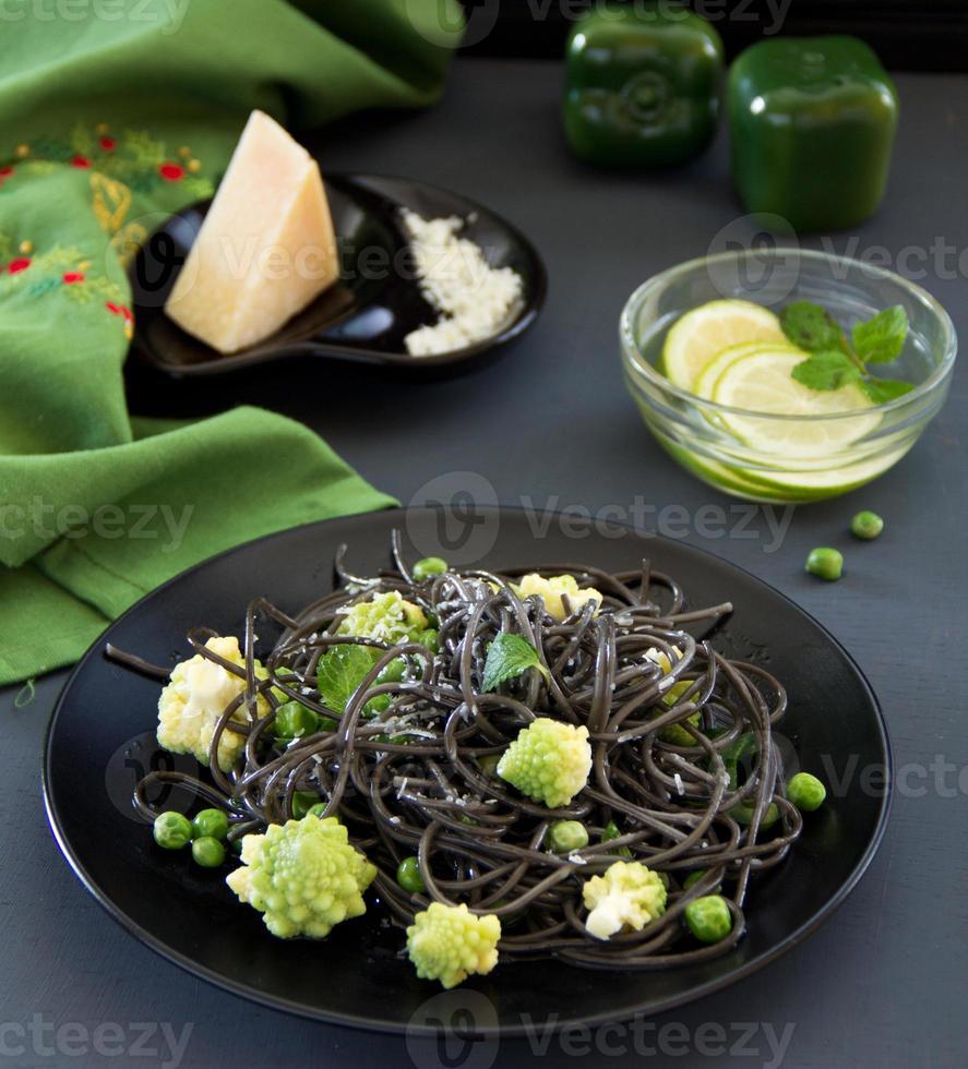 espaguete de tinta de choco com brócolis e ervilhas verdes. foto