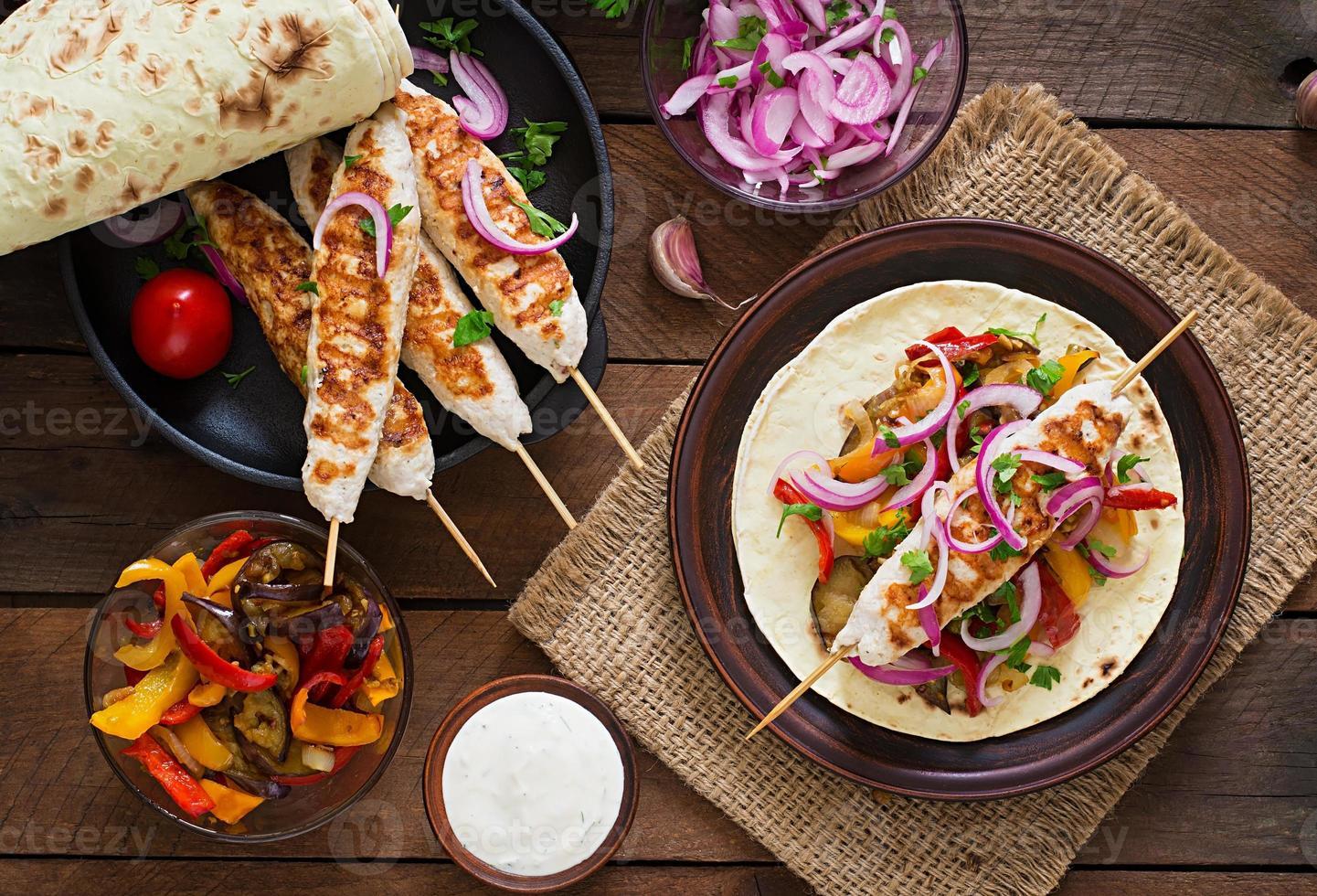 espetada de frango com legumes grelhados e tortilla wrap. foto