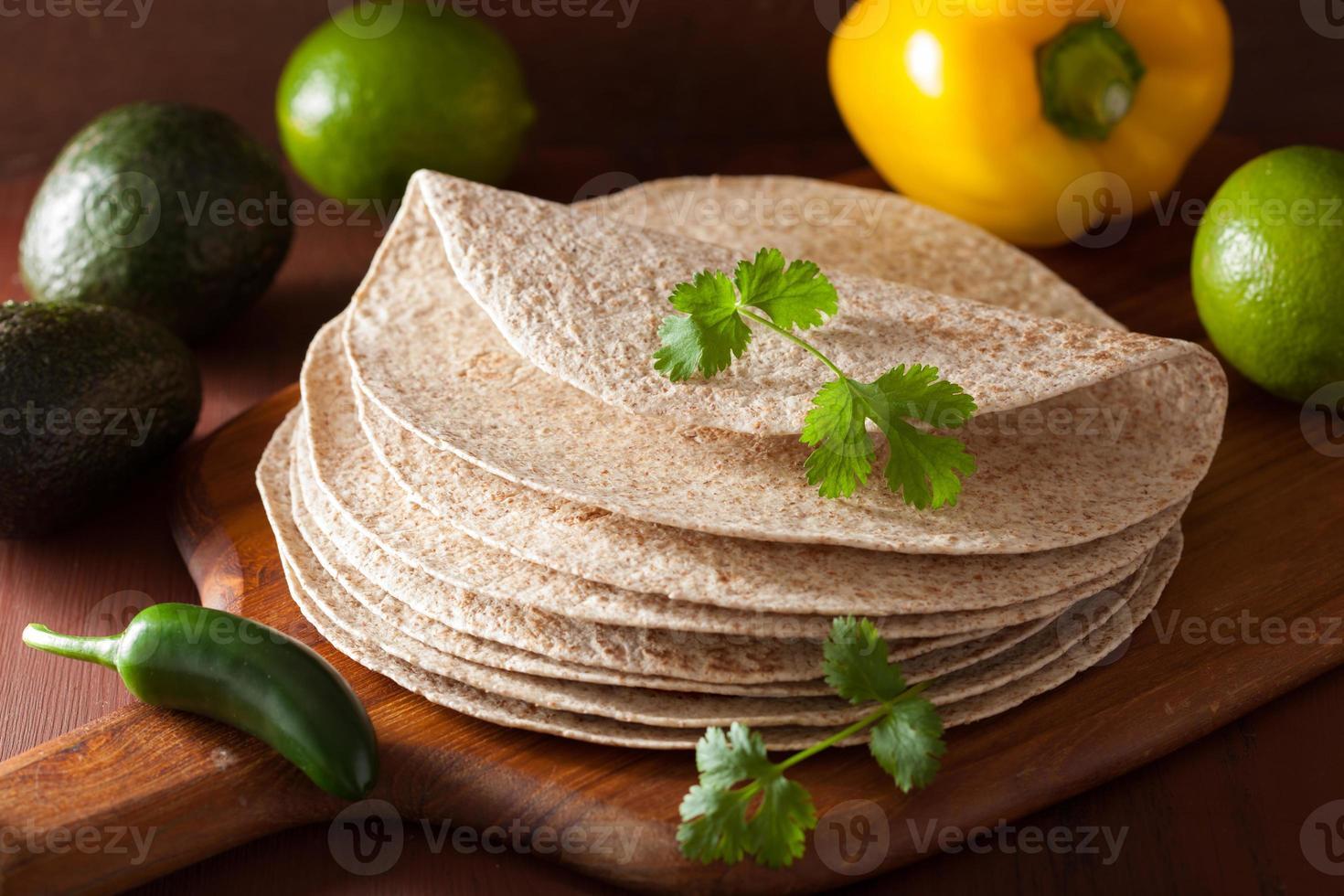 tortilhas de trigo integral na placa de madeira e legumes foto