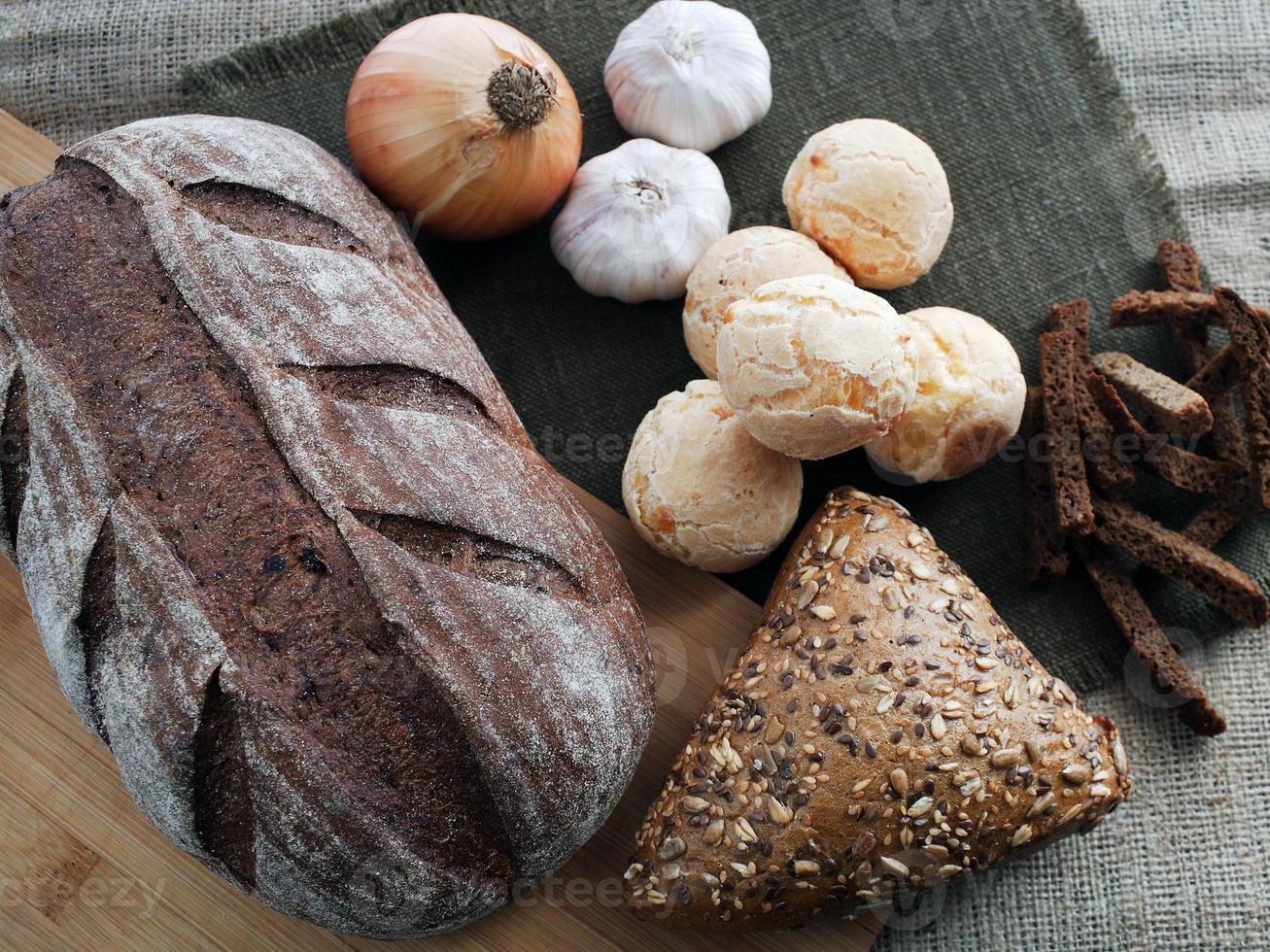 pão, cebola, alho e bolachas em um fundo marrom foto