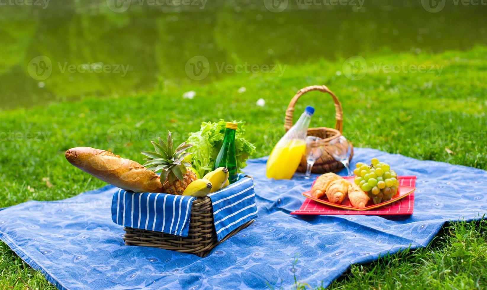 cesta de piquenique com frutas, pão e garrafa de vinho branco foto