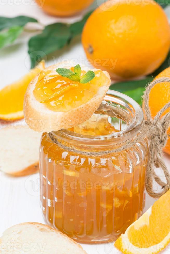 geléia de laranja em uma jarra de vidro e pão fresco, close-up foto