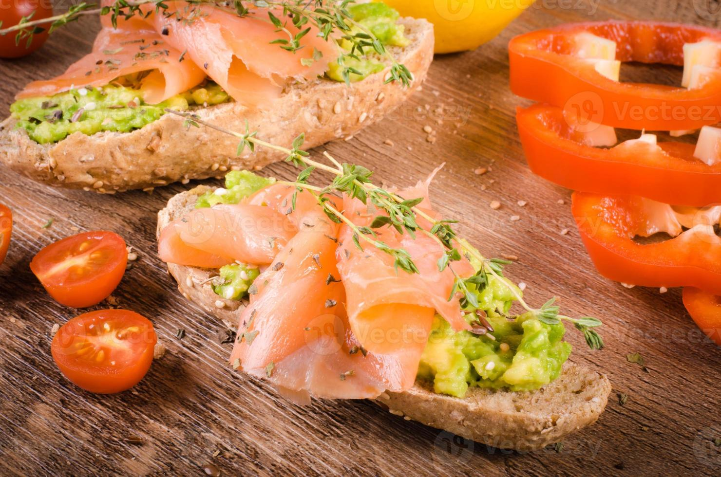 café da manhã: torradas de abacate com salmão em fundo de madeira. foto