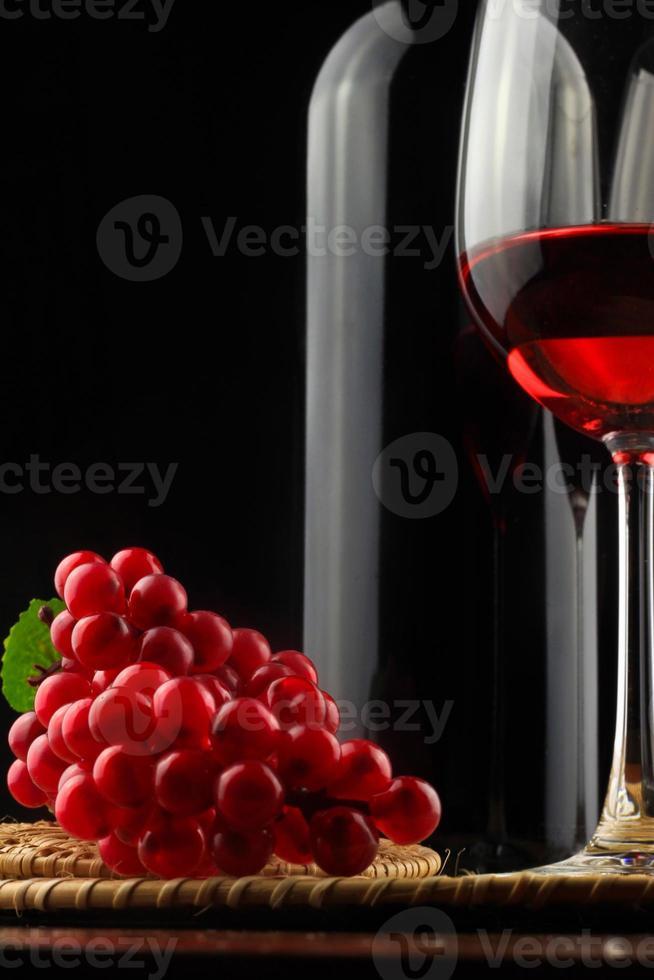 garrafa de vinho com um copo no fundo preto foto