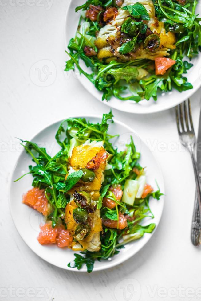 peixe grelhado com salada de rúcula foto