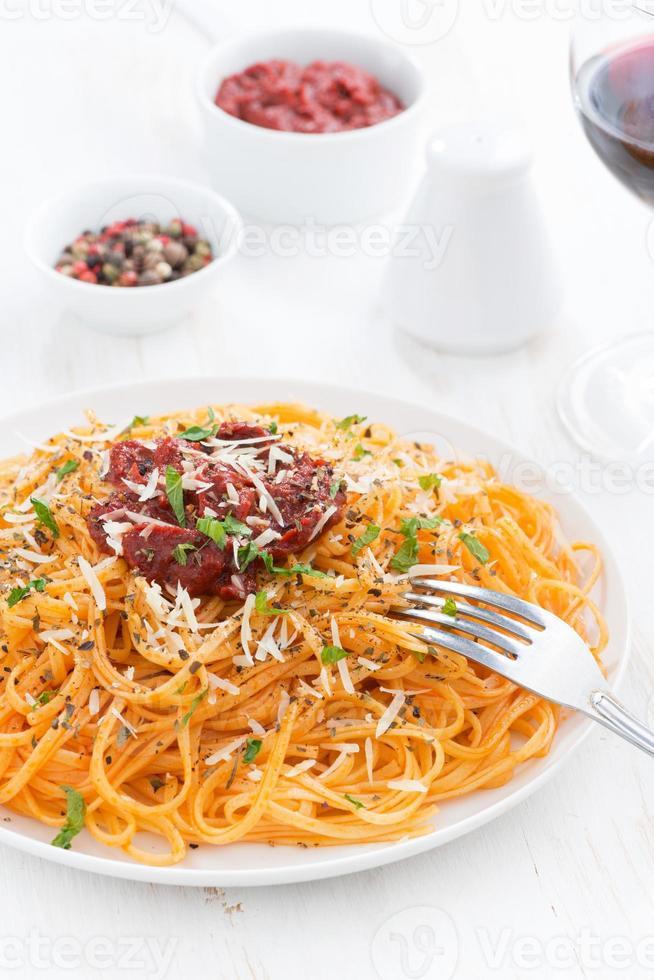 espaguete com molho de tomate e queijo parmesão no prato foto