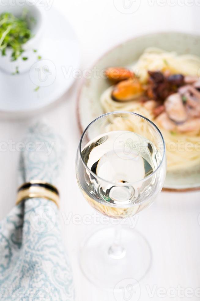 copo de vinho branco com macarrão de frutos do mar foto