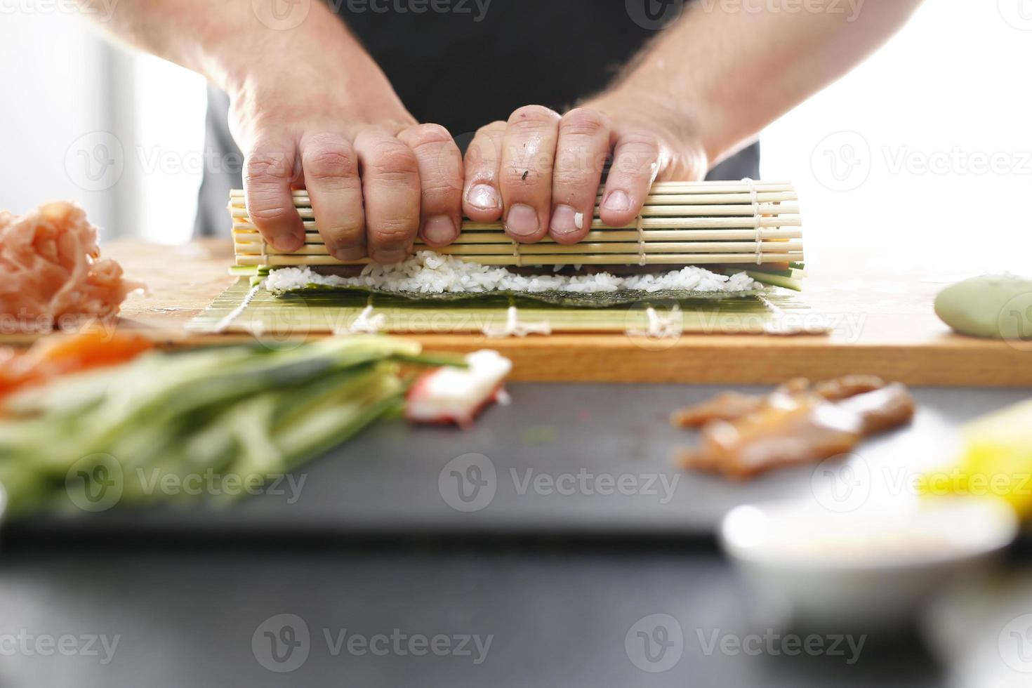 mestre de sushi prepara futomaki foto