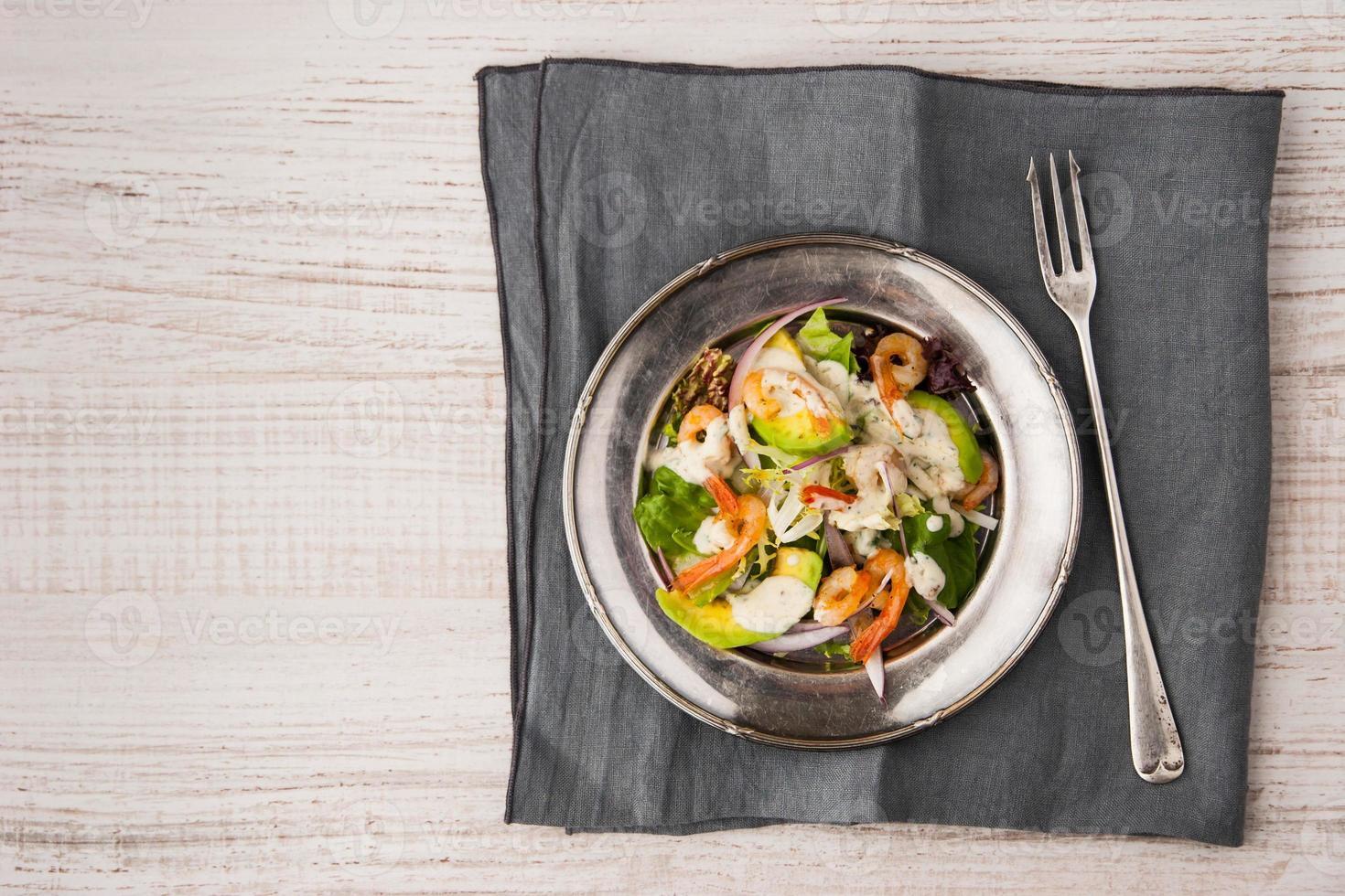 salada de fvocado e camarão no prato velho com garfo vintage foto
