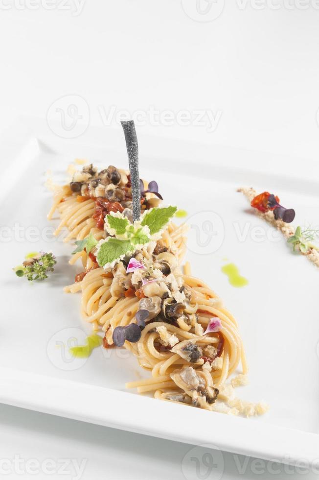 macarrão com frutos do mar em um prato branco, isolado no branco foto