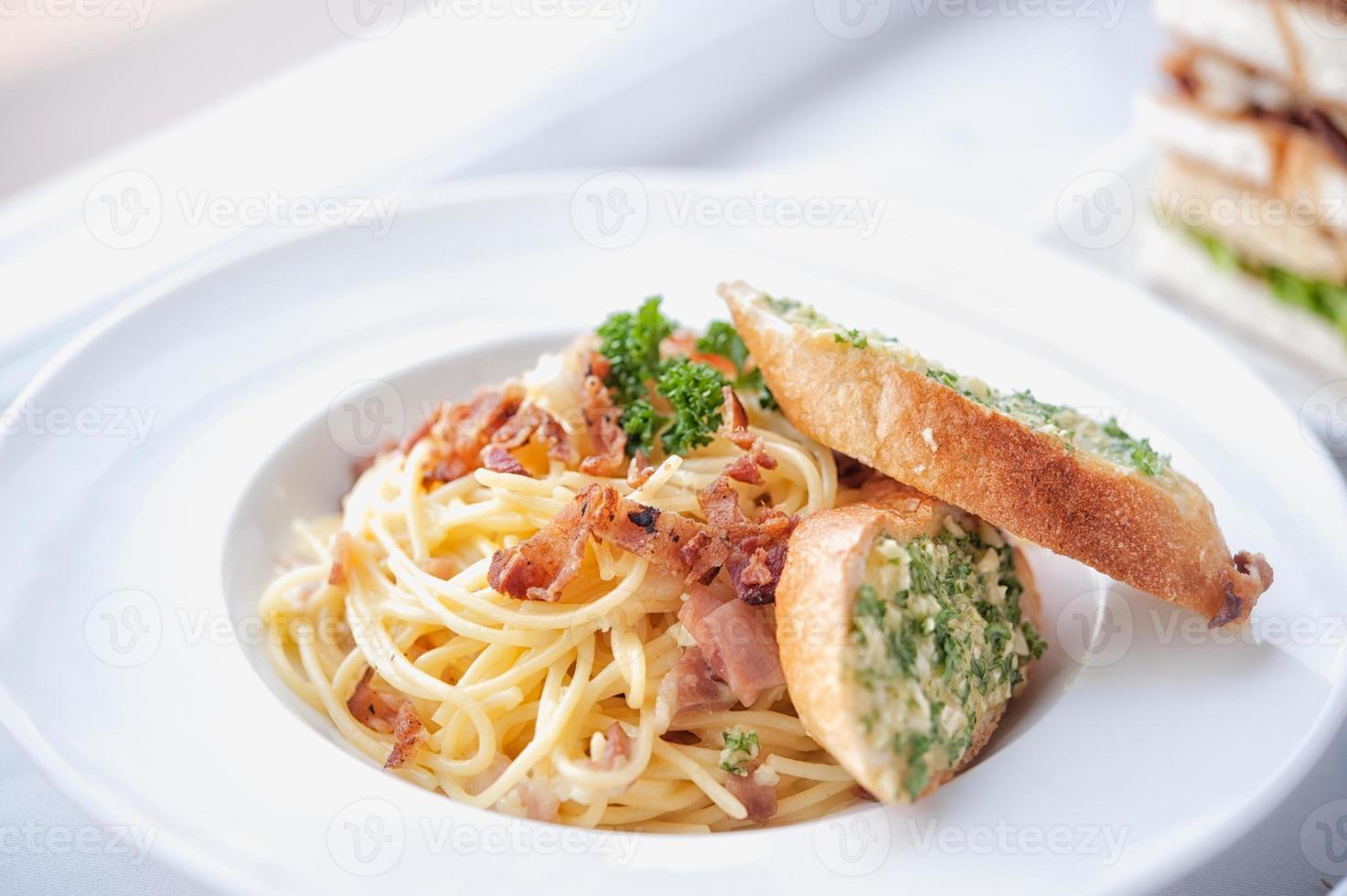 espaguete com bacon e pão de alho no prato branco foto