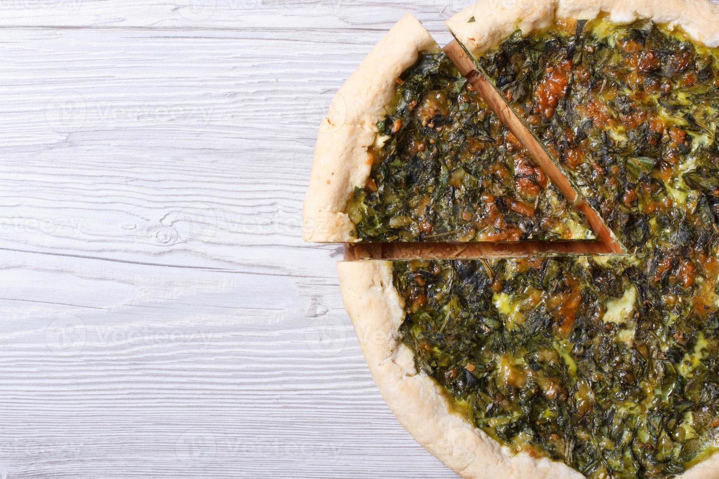 torta com ervas, queijo e espinafre close-up vista superior foto