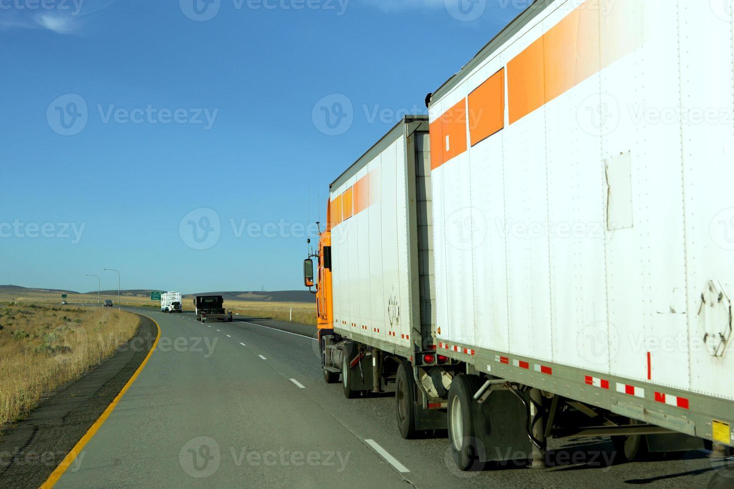 Vista lateral do caminhão dirigindo atrás de outros caminhões na estrada foto