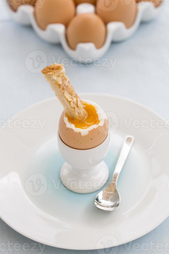 ovo cozido macio em eggcup com torradas na mesa foto