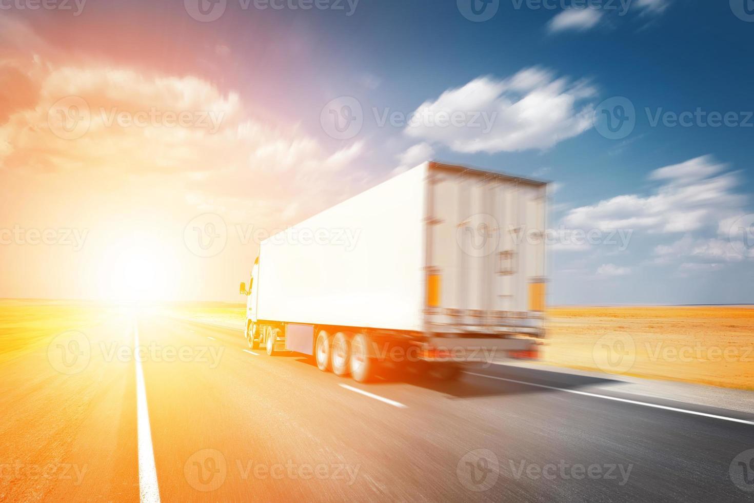 semitruck dirigindo ao pôr do sol foto