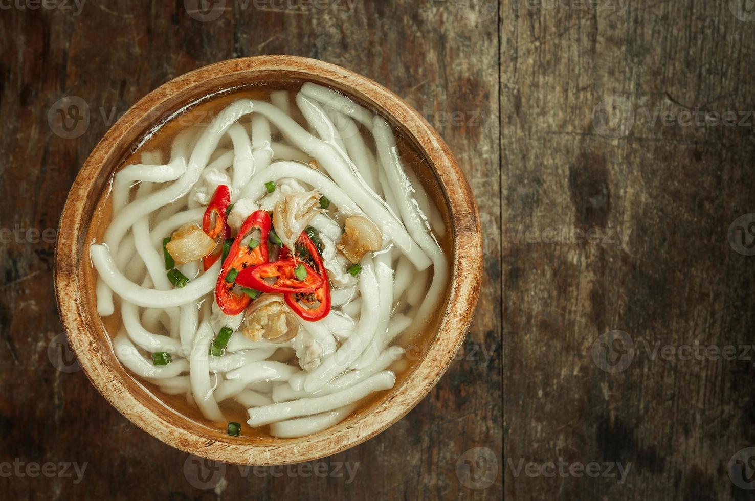 macarrão udon em uma tigela de madeira no fundo do assoalho de madeira foto