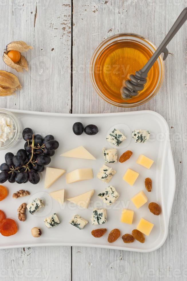 mistura de queijo e frutas no prato de cerâmico branco foto